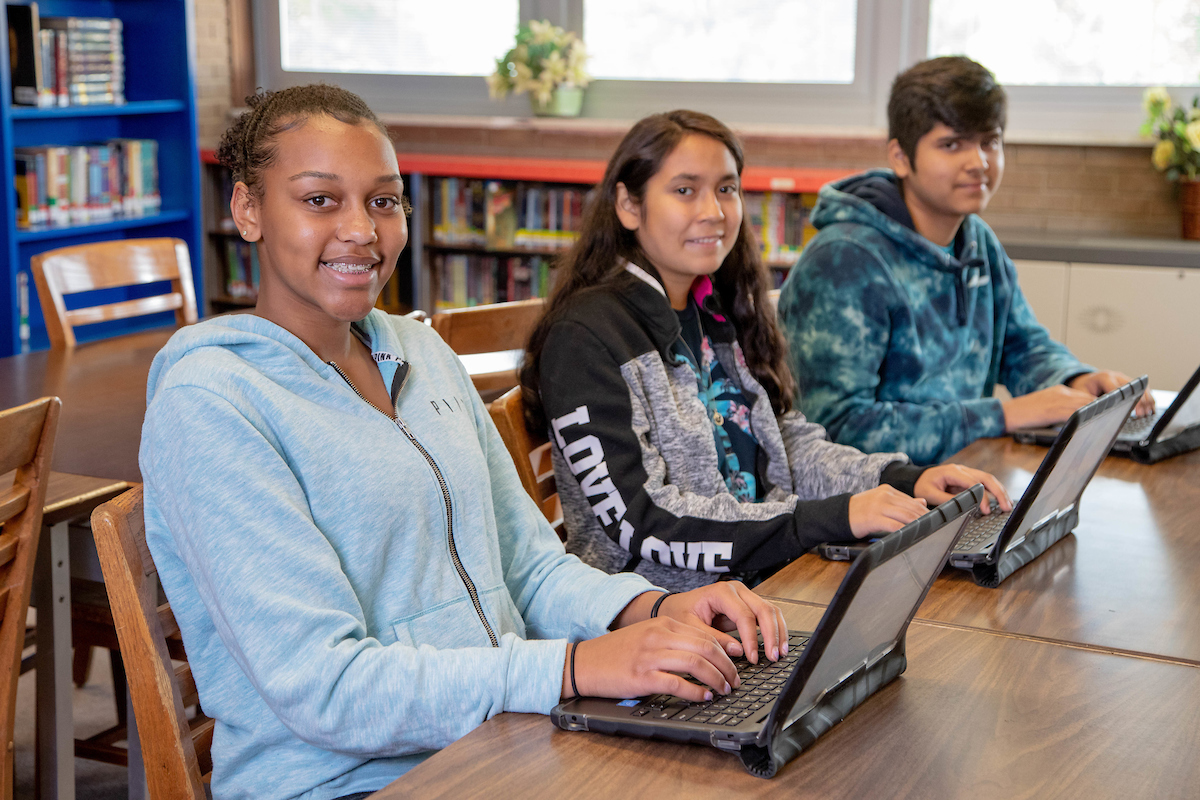 Three students working on laptops in class